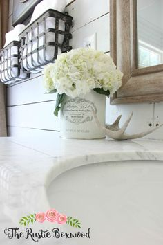 The Rustic Boxwood || Farmhouse style in the master bathroom -- hydrangeas, vintage sutliff can, marble, neutral elements and shiplap