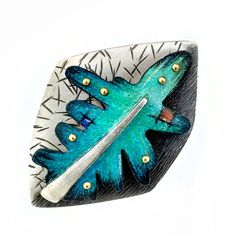 """This little leaf has an abundance of rich color and texture.  The color is a wax based pencil drawing on copper, sealed to maintain the beautiful colors.  Sterling silver, copper, brass, and Prismacolor.  2"""" x 1 1/2""""   $390 (2016)    Deb Karash"""
