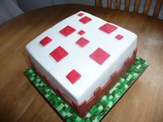 Minecraft Birthday Cake. Plain Minecraft cake from the game. Red and white design. The grass was made by first covering the cake board with green fondant, then mark out small squares before placing your cake on top, once your cake is decorated, fill 3 disposable icing bags with different shades of green icing and fill in the squares using a grass affect.
