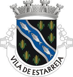 """Civic heraldry of Portugal - Brasões dos municípios Portugueses - Official blazon  Escudo de negro com uma banda ondada de azul orlada de prata carregada de três peixes, de prata realçados de negro, acompanhada de seis espigas de trigo de ouro folhadas de verde, postas em orla. Coroa mural de prata de quatro torres. Listel branco com os dizeres : """" VILA DE ESTARREJA """", de negro. Origin/meaning  The arms were officially granted on January 17, 1936."""