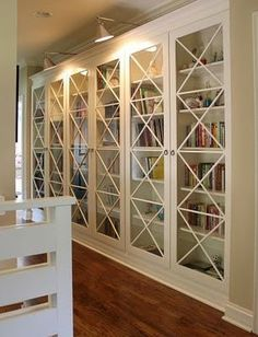 IKEA Billy bookcases with glass doors and added molding for a custom look.