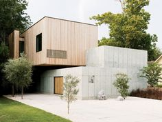 Designers Christopher Robertson and Vivi Nguyen-Robertson conceived their house as an unfolding sequence of simple geometric forms: a low concrete wall, a concrete cube, and a box clad in Siberian larch.