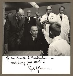 Left to right: Surgeon General Luther L. Terry, Senator Lister Hill, Johnson, unknown, Andrew G. Morrow, Fredrickson.  [Signed photograph of President Lyndon B. Johnson's visit to the National Institutes of Health]. Photographic Print. 1 Image. 9 August 1965.