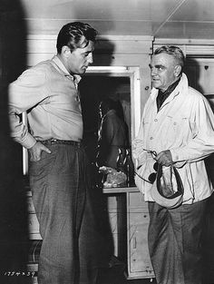 Robert Mitchum talks to James Cagney who visited him on the set of Home from the Hill, 1960.
