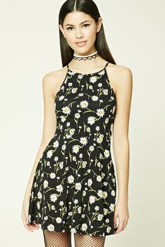 A knit cami dress featuring a daisy floral print, round neckline, and a flared skirt.