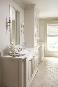 Sophisticated ensuite with herringbone pattern stone floors, pale gray walls paint color, light gray twin single bathroom cabinets vanities with desert sand honed and filled travertine countertops and glass canisters.