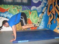 Encogimientos abdominales con trx (Crunch): Nos situamos boca abajo con manos en el suelo y pies colgando de los estribos del TRX. Encogemos las piernas hacia el pecho lo máximo posible y subimos la cadera