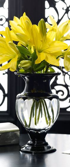 yellow lilies in a clear and black vase .  decorating black, yellow, grey, white