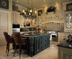 Such a beautiful kitchen. Love the center island, and the above-cabinet decor adds interest and color to the room.