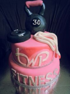 Fitness themed cake complete with kettle bell, barbell plate and skipping rope. Sparkly ribbon for an all women's gym.