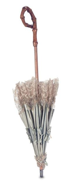 Wooden handled parasol with faux-bamboo hand-grip in a fanciful design is fitted with original aqua silk cover and ribbon rosettes and edged with a wide border of Alencon lace. Excellent condition. French,circa 1885.