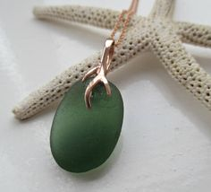 Eye-catching, unique rose gold vermeil (Over sterling Silver) green sea glass pendant with 18 rose gold filled chain  The seaglass is hand collected from the beaches of North East England. Each piece of seaglass that gets washed up on the shore is unique therefore it creates a one of a kind piece of jewellery to be treasured.  An ideal gift for a special occasion.   Where does the seaglass come from?  Seaham was noted for its glass producing factories in the mid 1800s, but closed in 1921…