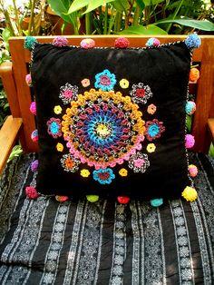 crocheted embellishments on cushion cover - pom-poms too! I like the black velvet background...can imagine something like this on the back of a velvet jacket!