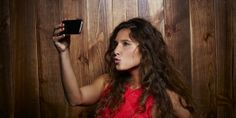 Woman taking a selfie for online dating profile, Mads Perch,Getty Images // Woman taking a selfie for online dating profile, Mads Perch,Gett...
