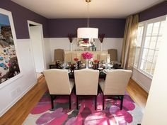 Purple reigns in this contemporary dining room. Purple walls and a purple and magenta rug contrast with the neutral chairs and black dining table. A pendant light with a drum shade and an ivory sideboard complete the look.