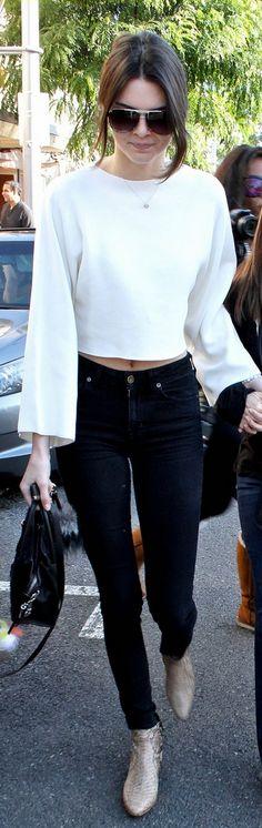 Kendall Jenner, black handbag, key chain, and snake print boots