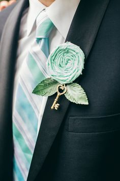"""The boutonnieres were handmade by the bride. """"I used little keys as the stem and made mint fabric flowers from leftover fabric from the ring bearer pillow I made,"""" she says. 