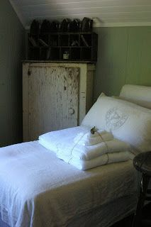 Farmhouse Fresh... old worn cupboard and lovely white linens....against the green walls