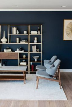 living room with navy walls & open-back bookshelves