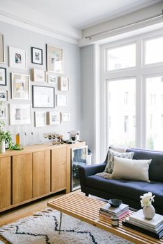 Navy sofa with midcentury buffet and gallery wall