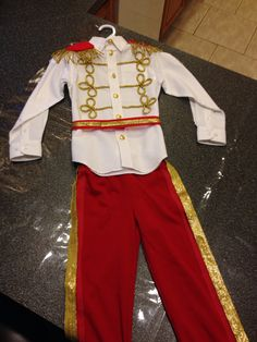 Homemade Prince Charming costume. Red pants with gold ribbon applied with Velcro. Sewed on gold buttons and applied all other accents applied with a hot glue gun.