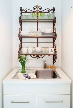 An easy way to decorate a simple bathroom with glam and charm: Find a nice wire piece to hang over the sink or toilet next to or in place of a mirror for extra storage space!