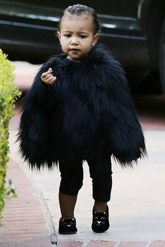 North takes childrenswear to the next level in a black fur cape styled with Charlotte Olympia cat loafers. Talk about the best-dressed kid on the playground...   - HarpersBAZAAR.com