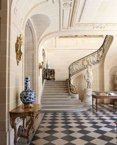 Camondo: The foot of the main staircase in the entrance hall. This view demonstrates French preferences for the first space in a house perfectly: As a transition from outside to in, its an architecturally treated interior of exterior materials. The stone-look can be real or faux. Furnishings are scant and impersonal, yet it's elegant and welcoming. JC