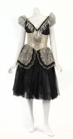 A masquerade ball dancer costume from The Phantom of the Opera (Warner Bros., 2004). The black and white dress has a butterfly embellishment at stylized corset, small white apron, and short off-the-shoulder sleeves. No size or label present.