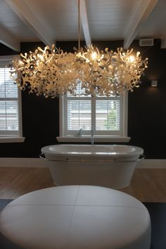 Enorme poef als middelpunt van badkamer. Alle functies van de badkamer zijn gegroepeerd rondom de enorme witte poef die daarmee het middelpunt van de badkamer vormt. Om deze centrale plek extra te accentueren hangt boven het zitmeubel een prachtige moderne kroonluchter die tevens zorgt voor sfeervolle licht.