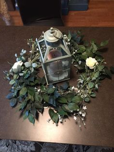 This is perfect! Cassie Haggerty's wedding in St. Cloud. The greenery is all Hobby Lobby clearance items. Swap the lantern for 2-3 candles per table. Eucalyptus, green leaves, and gypsophila around a metal wreath base. I'd maybe do Laurel leaves since they're cheaper than Eucalyptus.