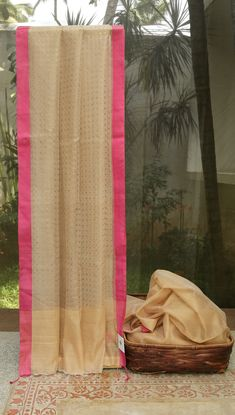 This latte tan kora sari has a plain body with the tan blouse. The pallu is latte tan with gold sequin work and hot pink border runs throughout the sari which gives a modern finish and young look .