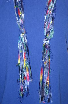 Yarn scarf,  Bright Tomorrows, is a knotted ribbon yarn scarf, the main color of which is blue with other primary colors mixed in.. $18.00, via Etsy.  (Inspiration Only)
