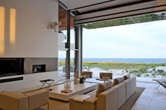 This modern beach house with an airport glass hanger door in the living room has been designed by West Chin Architects, located in Long Beach, New York. Living Room New York, Home Living Room, Living Room Designs, Low Coffee Table, Coffee Table Design, Open House Plans, Bungalow, Long Beach, Eco Friendly House