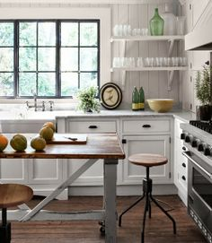 Farm style kitchen in whites with wooden board backsplash and open shelves. Replace island with rustic table.