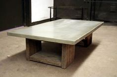 James De Wulf - Scaffolding Coffee Table  Price: $1,550.00 This table is a nice juxtaposition of materials with a smooth refined concrete top on a reclaimed scaffolding plank base. Suitable outside.