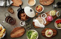 Anret alt fyldet, f.eks. pulled pork, løg, peberfrugt, salat, salsa og coleslaw i glas og skåle, og gå i gang med at fylde tortilla'erne.