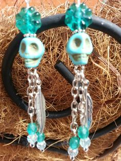 Turquoise skull earrings with chain dangles and feathers.