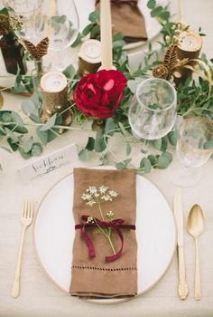 Elegant woodsy theme accomplished by natural napkin wrapped with dark velvet ribbon, embellished by a little sprig of Queen Anne's Lace or similar flower, also accompanied by goblets and delicate calligraphy on place cards.