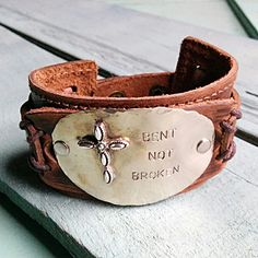 """Bent Not Broken Distressed Leather Cuff Bracelet features a hand stamped plate attached with two nickel rivets. Genuine leather cuff measures 2"""" x 9"""" Adjustable to 7"""" and 7.5"""" Disc measures approx. 1."""