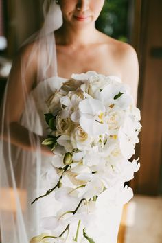 Elegant all-white orchid bridal bouquet perfect for a beach destination wedding {Facebook and Instagram: theweddingscoop}