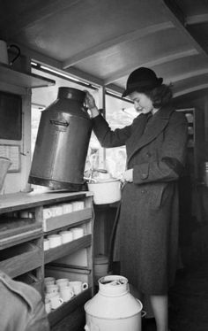 Patience 'Boo' Brand fills a large saucepan with water from the urn on board the mobile canteen that she and her friend run on behalf of the Women's Voluntary Service, as men of the Pioneer Corps gather outside. In front of her, another urn and stacks of mugs can also be seen.