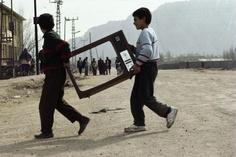 """Turkey. Kurdistan. Dogubayazit. 1993. Two Kurdish boys cross a road, carrying the frame of a television screen"" by Reza/ Webistan"