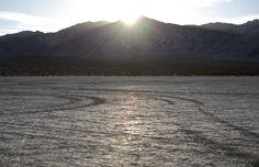When this lake dried up, little pools of dried salt formed at the bottom of the cracks. As the sun set over the mountain behind it, at just the right angle, all that salt reflected white light and gave it the appearance of a frozen lake.