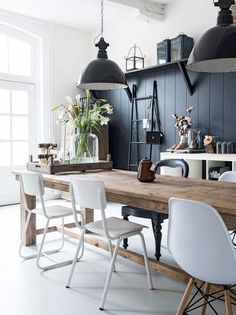black industrial lights with black wall in modern barn house with white walls and mismatched white chairs. / via @sfgirlbybay