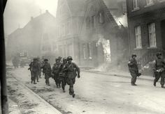 Troops of the 17th U.S. Airborne Division, First Allied Airborne Army, march past a blazing building in Appelhulsen, Germany, as they advance toward the city of Munster, nine miles to the northeast.