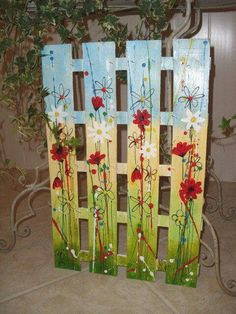 Pallet painted gate decoration, with flowers, green grass and sky.