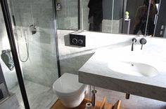 Un grand miroir reflète la luminosité de la salle de bains parentale - Duplex parisien totalement relooké pour une famille - CôtéMaison.fr
