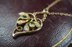 A gorgeous Art Nouveau peridot & seed pearl set mistletoe necklace. Now online! CJAntiquesLtd.com #antique #artnouveau #gold #pearl #peridot #pendant #necklace #antiquejewelry #jewelsofinstagram