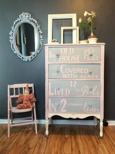 "I loved the book ""Madeline"", so I put the opening line on the dresser front!  It is painted in pink, gray, and off white."